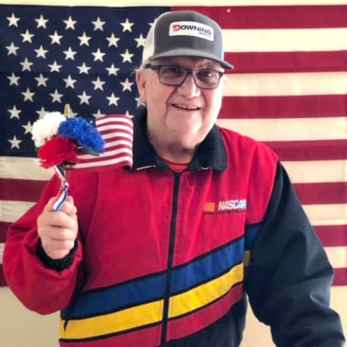 Resident in front of an american flag, holding a smaller american flag at Ashbrook Village in Duncan, Oklahoma