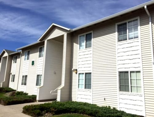 Beautiful white exterior with a well manicured landscape at Autumn Run Apartments in Great Falls, Montana