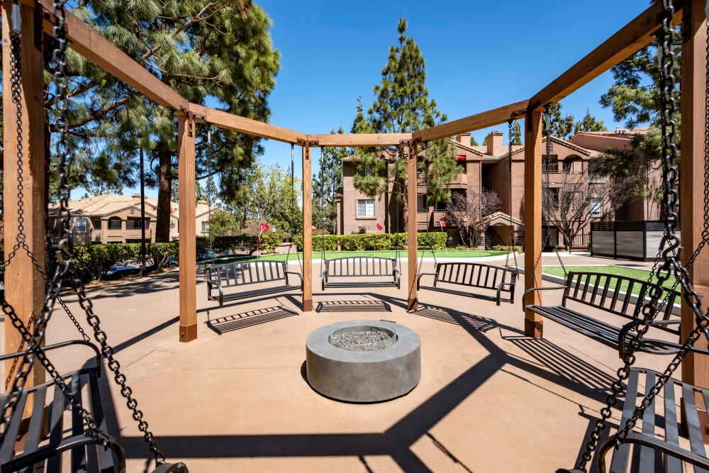 A fire pit surrounded by swings at Sierra Del Oro Apartments in Corona, California