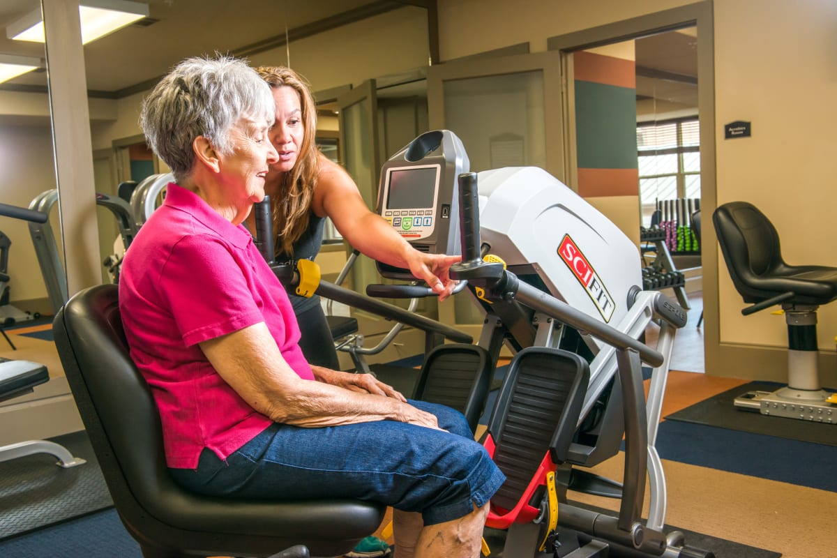 Resident learning how to use fitness equipment at an Integrated Senior Lifestyles community