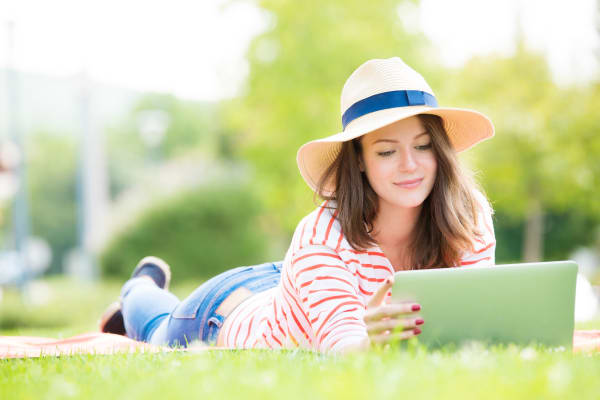Smiling young woman lying on the grass and using her laptop near Warner Village Apartments in Trenton, New Jersey