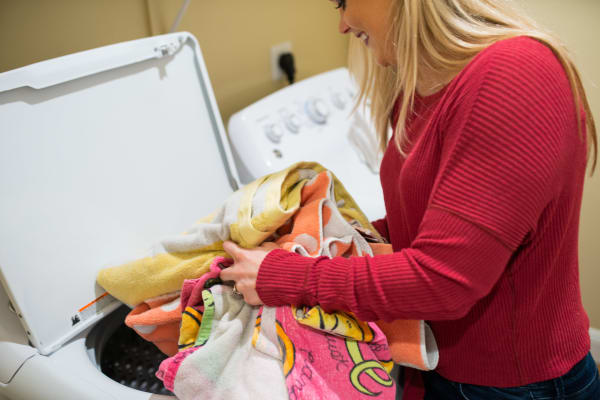Resident doing laundry in her new home at San Marquis in Tempe, Arizona