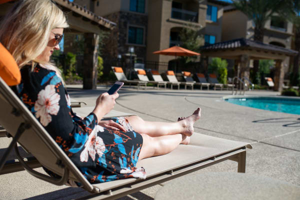 Resident surfing the web on her phone near the pool at San Privada in Gilbert, Arizona