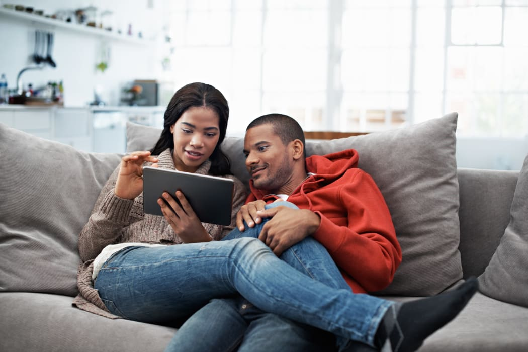 Young couple using their tablet while sitting on the sofa at Presidential Court home in Runnemede, New Jersey