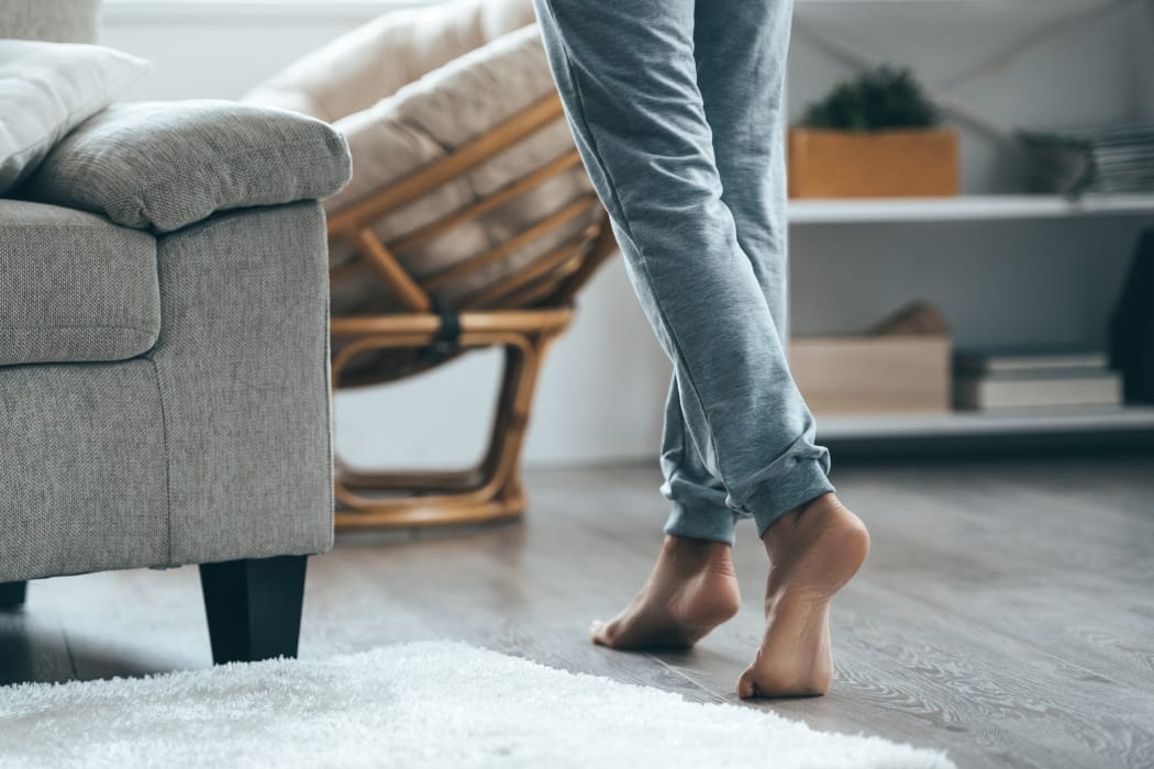 Resident walking by hardwood floor at Veridian Place home in Dallas, Texas