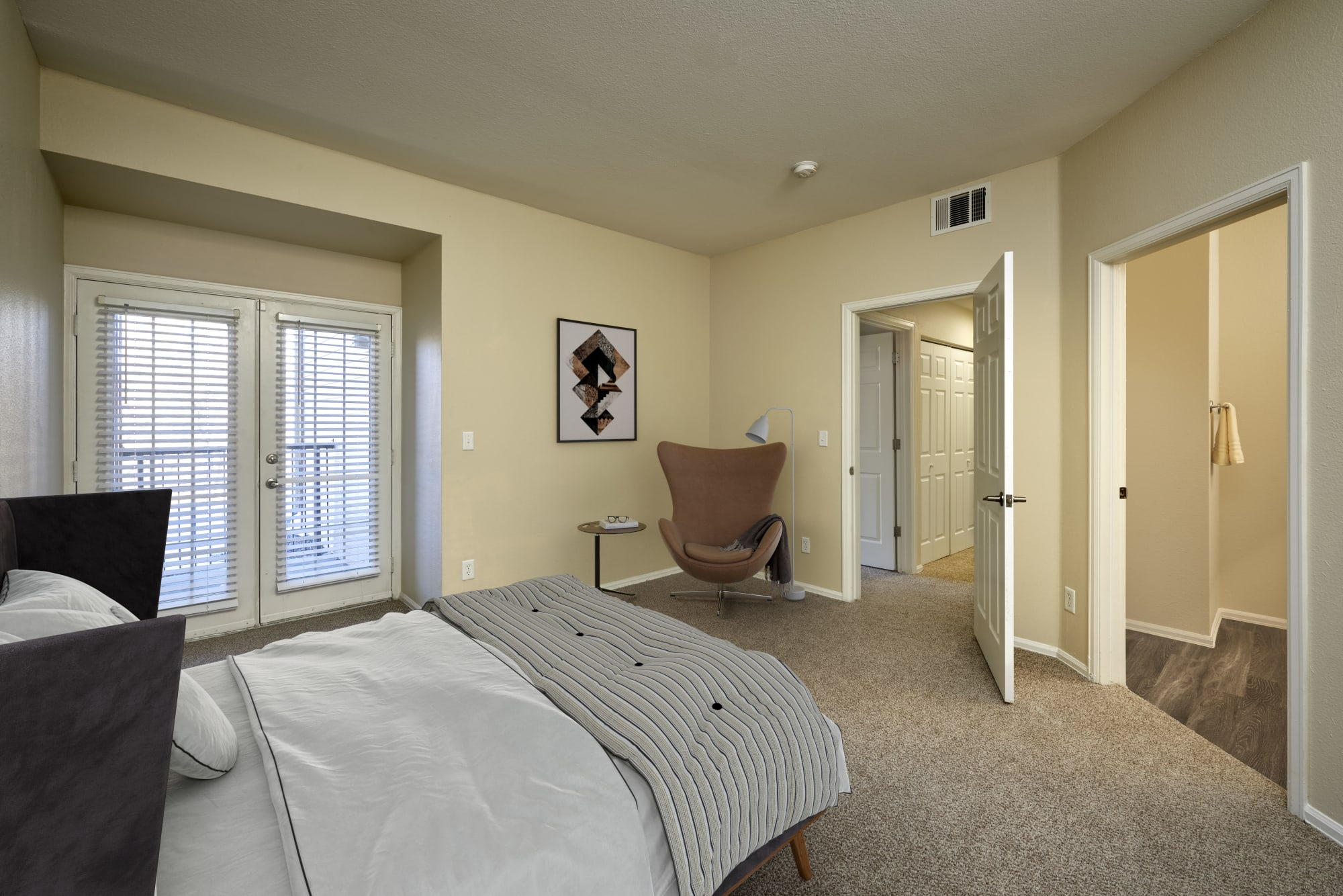 A spacious master bedroom with a bathroom at The Crossings at Bear Creek Apartments in Lakewood, Colorado