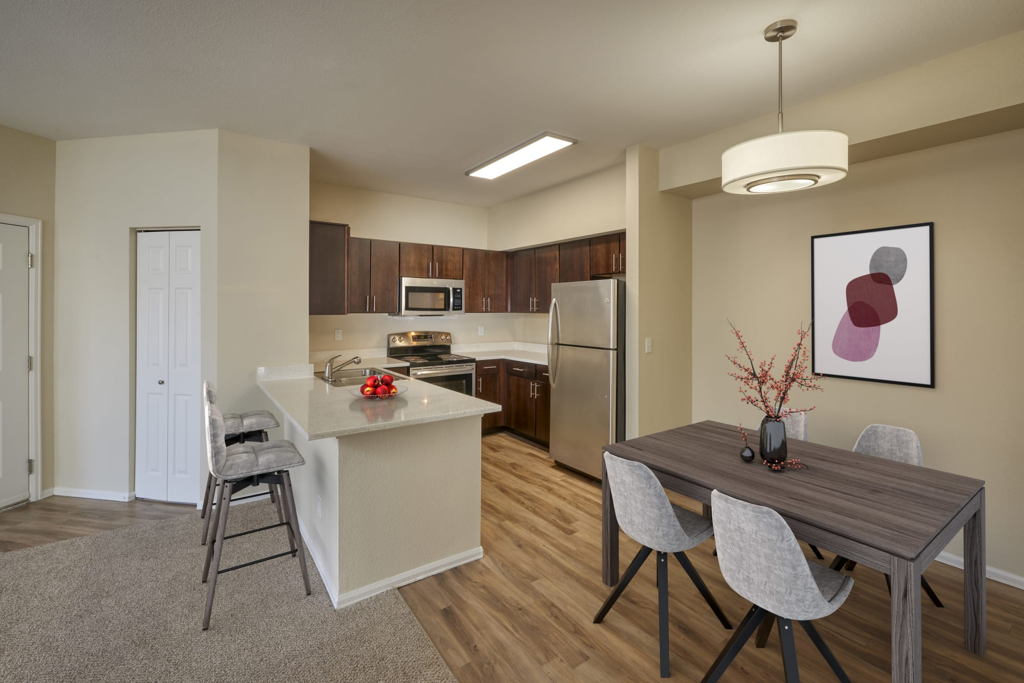 A renovated kitchen with brown cabinets and stainless steel appliances at The Crossings at Bear Creek Apartments in Lakewood, Colorado