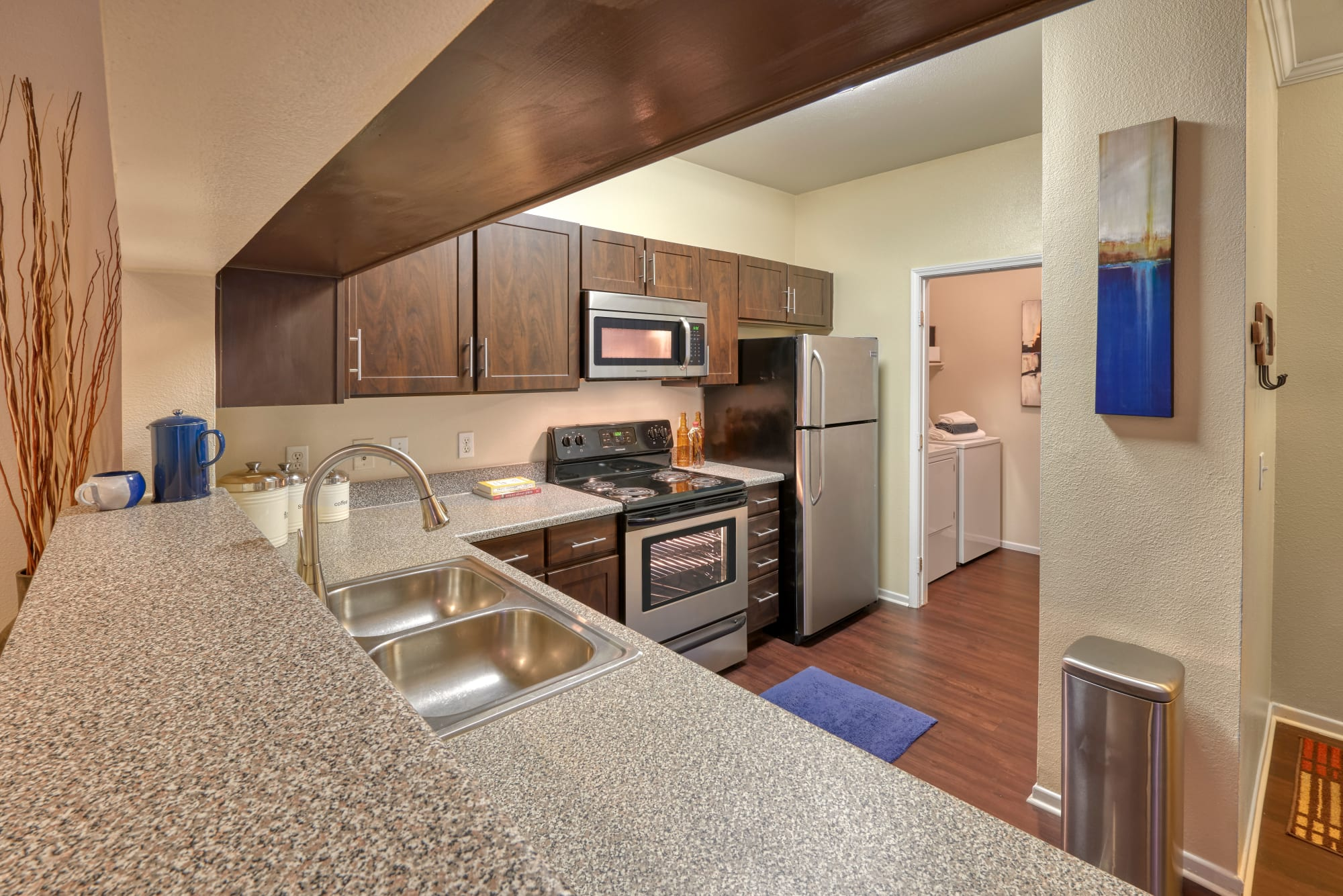 Espresso-colored cabinetry and granite countertops on display in this kitchen at Hawthorne Hill Apartments in Thornton, Colorado