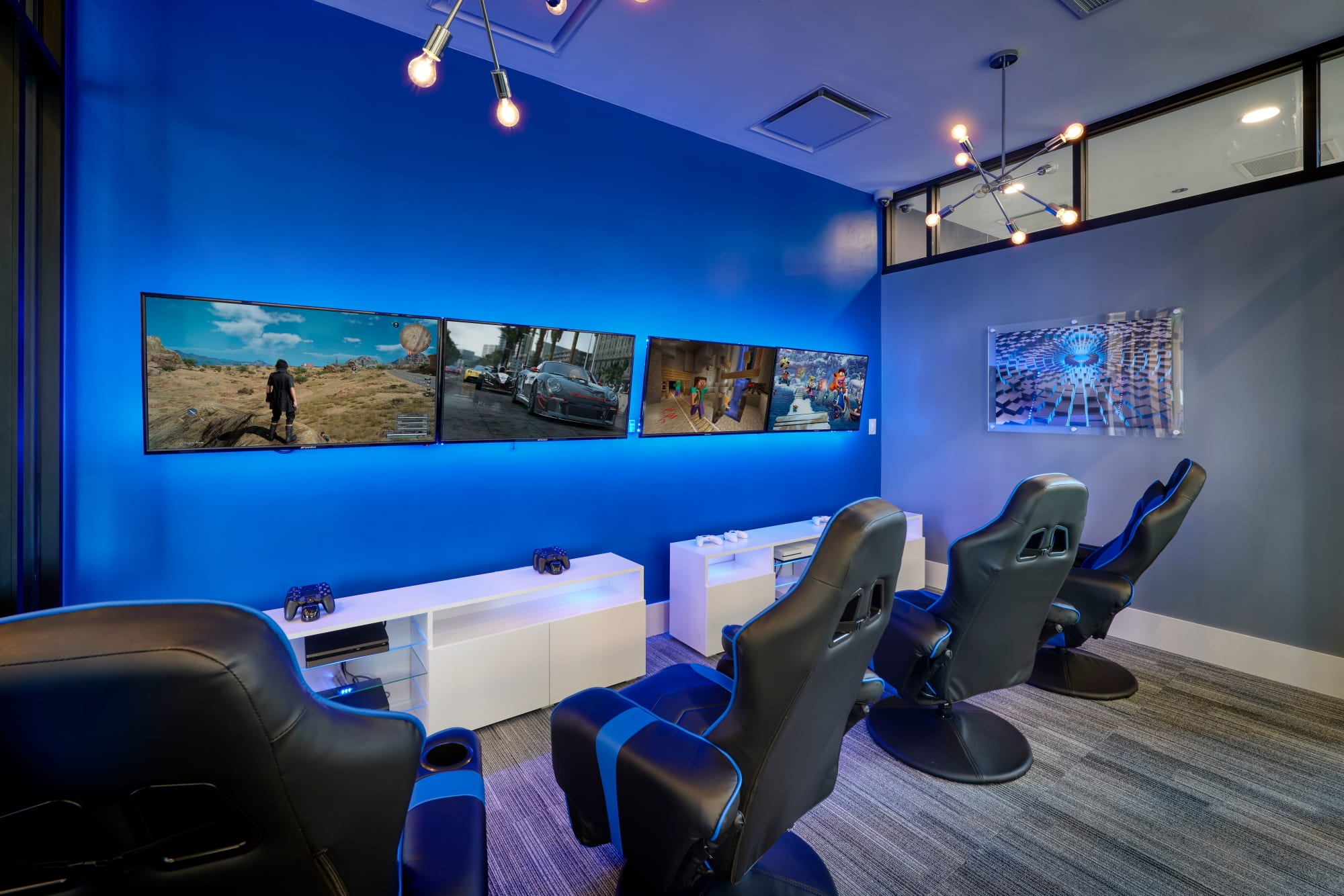 The video room, with consoles and gaming chairs, at Strata Apartments in Denver, Colorado