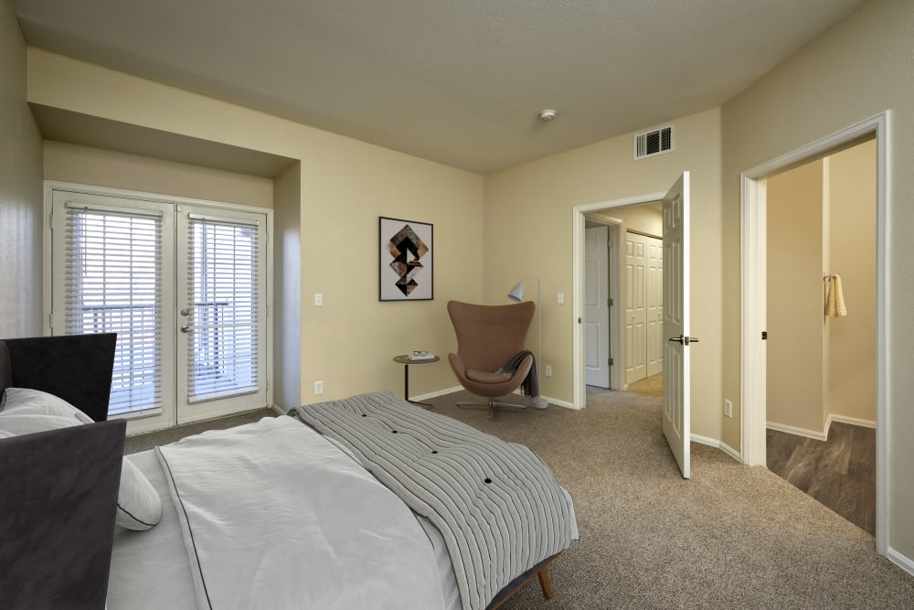 Master bedroom with an attached bathroom at The Crossings at Bear Creek Apartments in Lakewood, Colorado