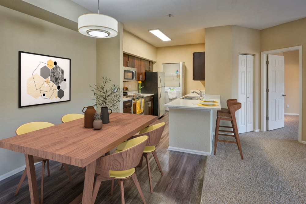 Dining room with wood-style flooring at The Crossings at Bear Creek Apartments in Lakewood, Colorado
