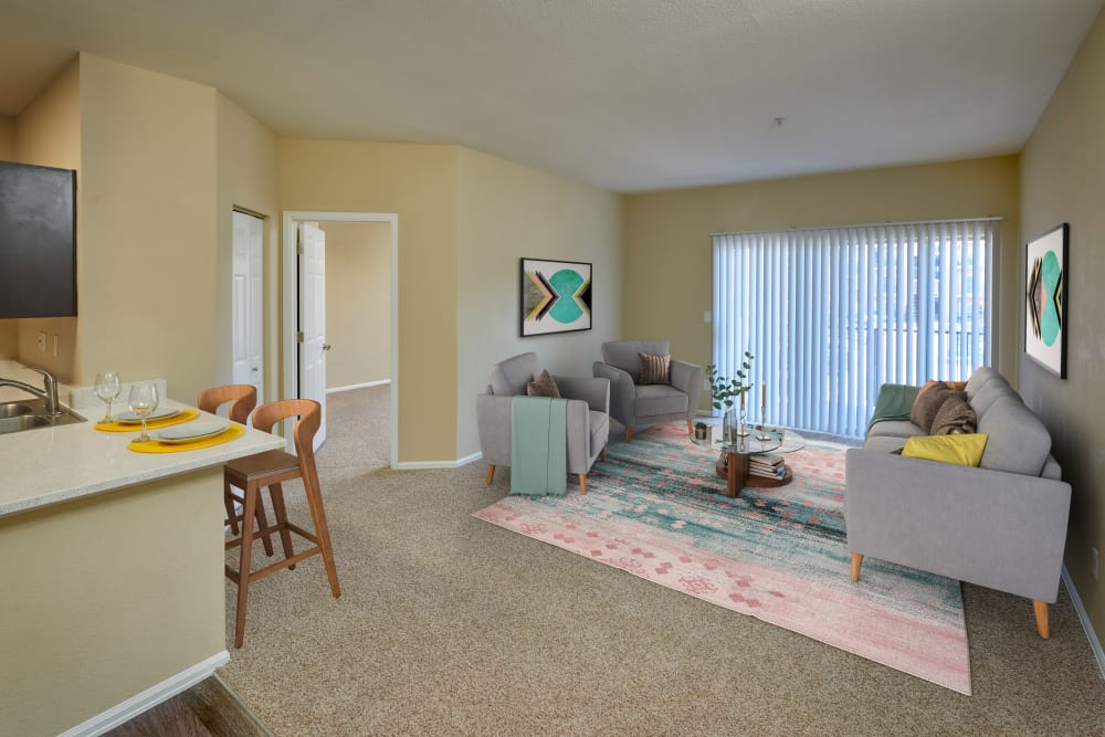 Living room with plush carpeting at The Crossings at Bear Creek Apartments in Lakewood, Colorado