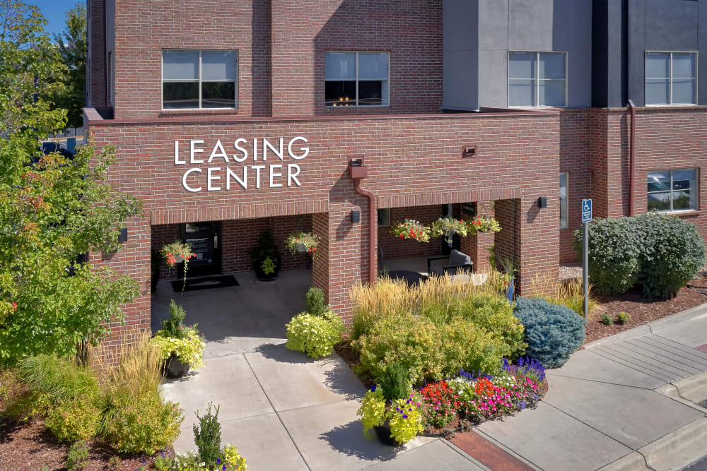 Leasing center entrance surrounded by a lush green landscape at The Rail at Inverness in Englewood, Colorado