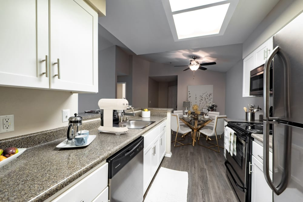 A kitchen looking into a dining room at Sierra Del Oro Apartments in Corona, California