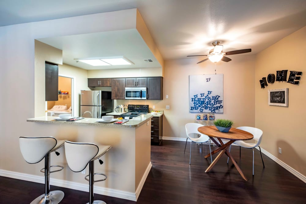 Bar-top seating looking into a kitchen at Sierra Del Oro Apartments in Corona, California