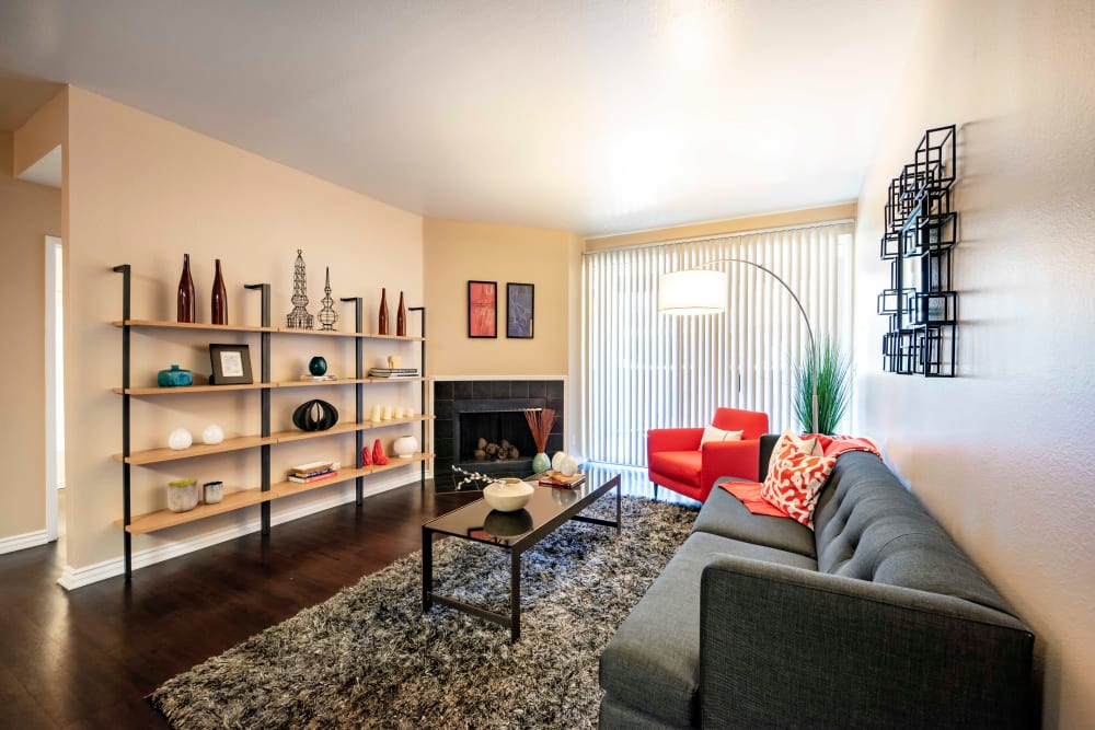 A living room with a fireplace and private patio access at Sierra Del Oro Apartments in Corona, California