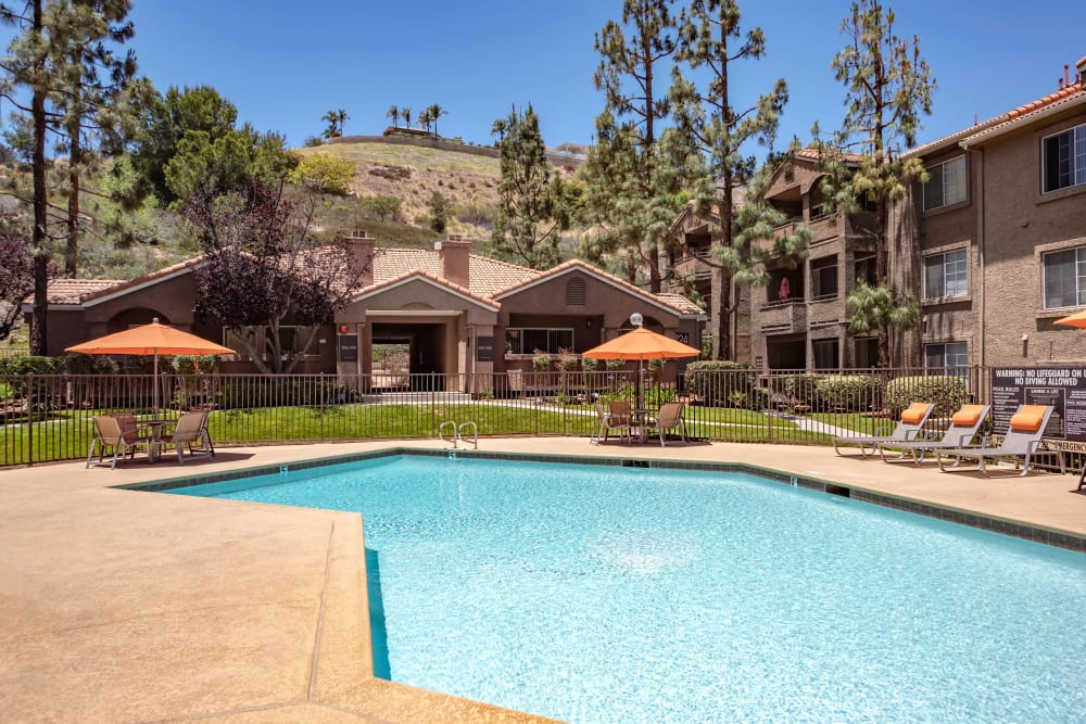 Beautiful resort-style swimming pool with lounge chairs and tables with umbrellas at Sierra Del Oro Apartments in Corona, California