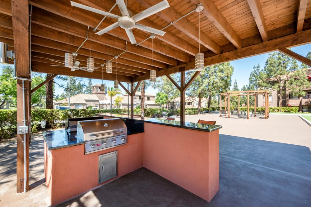 Covered grilling area with bar top seating and a fan at Sierra Del Oro Apartments in Corona, California