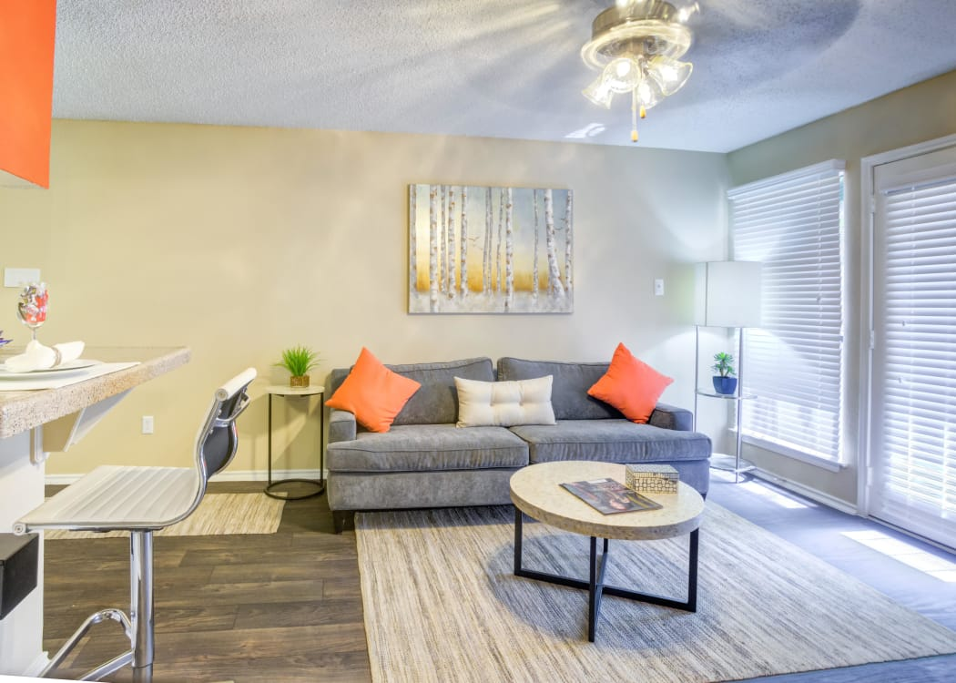 Spacious living room with wood-style flooring at Enclave at Water's Edge Apartments in Austin, Texas.