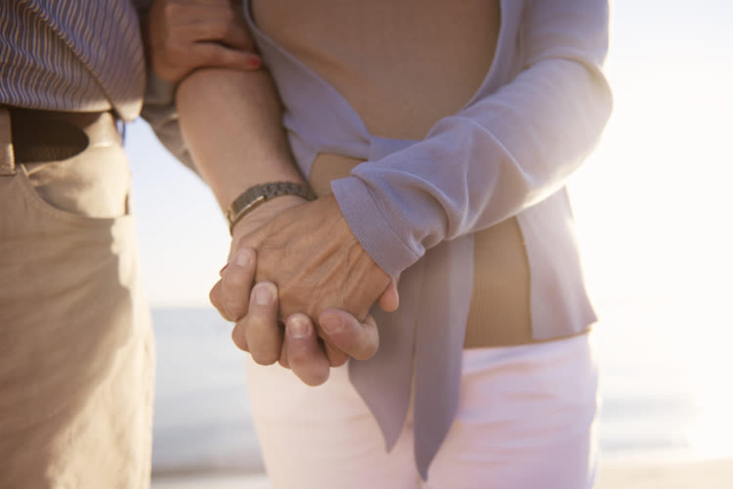Seniors holding hands on the beach at MBK Senior Living in Irvine, California