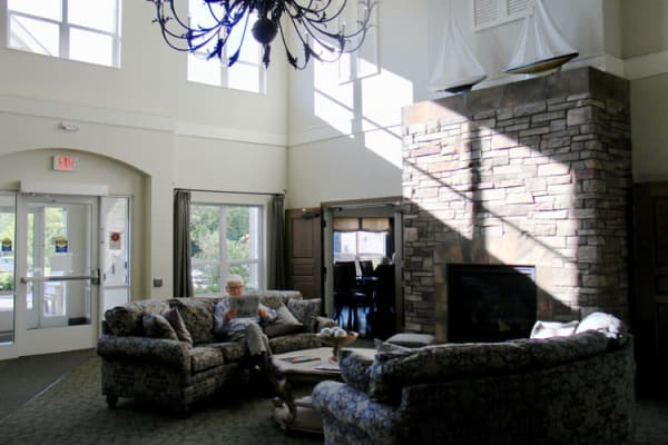 Sunlit lounge with a fireplace and vaulted ceilings at Deephaven Woods in Deephaven, Minnesota