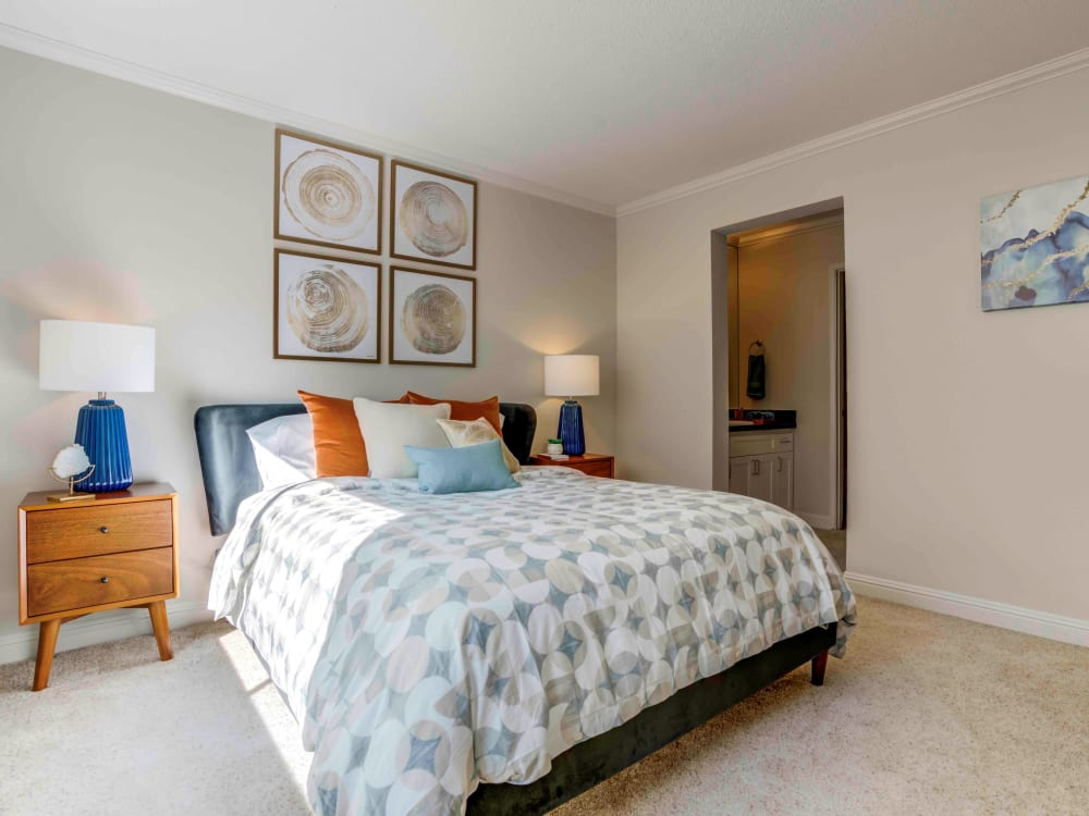 Well-decorated master bedroom with plush carpeting and mirrored closet doors in a model home at Sofi Redwood Park in Redwood City, California
