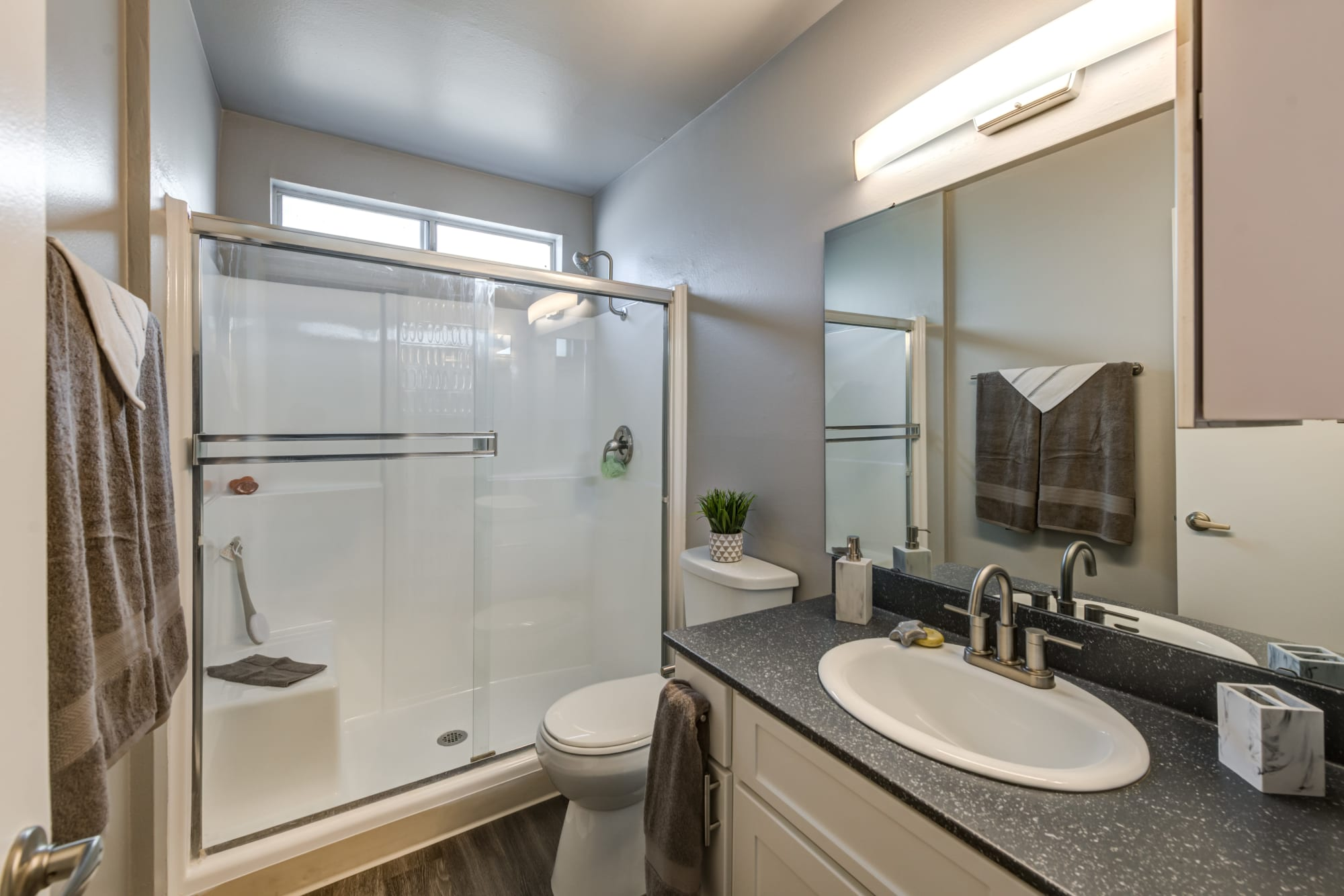 A renovated bathroom with white cabinets at Kendallwood Apartments in Whittier, California