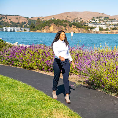 Resident going for a walk on one of the paths along the bay at Harbor Point Apartments in Mill Valley, California