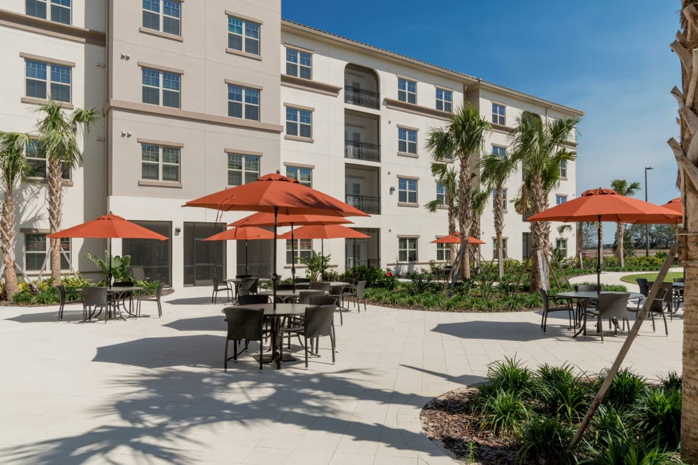 patio with tables and lounge chairs at Merrill Gardens at ChampionsGate in ChampionsGate, Florida.