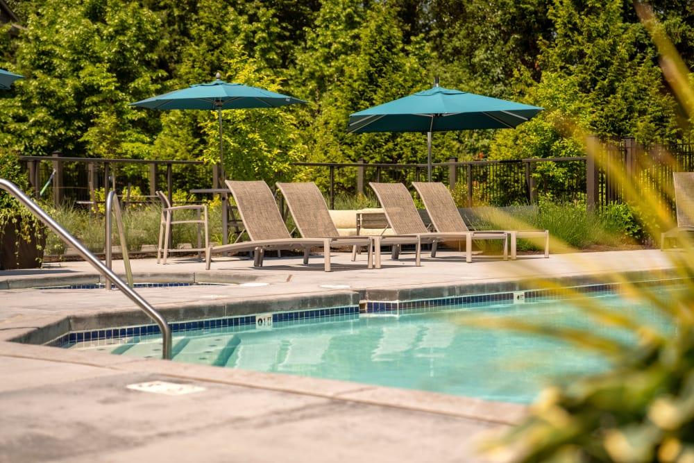 Beautiful resort-style swimming pool with lounge chairs at Brookside Village in Auburn, Washington