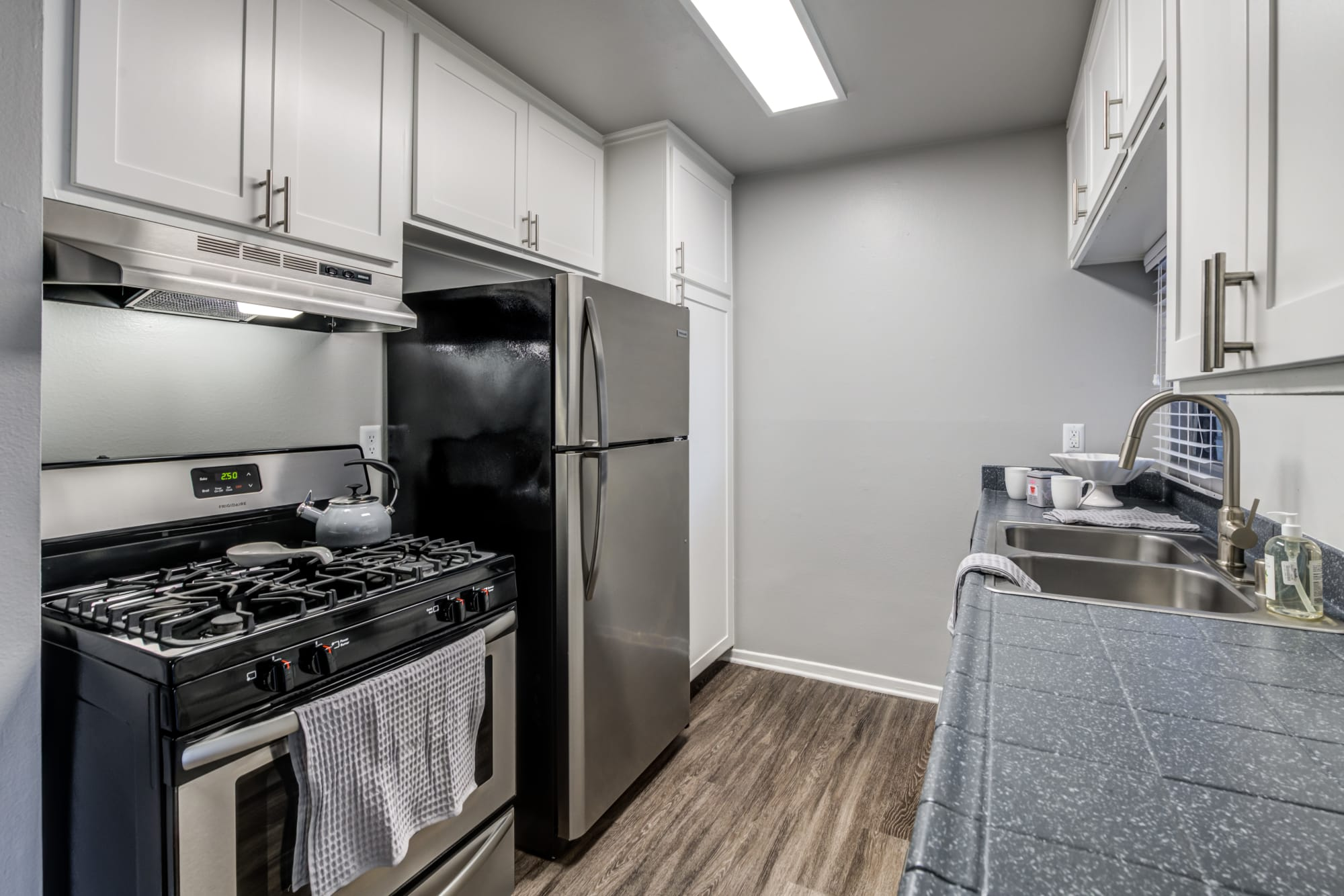 Renovated kitchen with white cabinets and stainless steel appliances at Kendallwood Apartments in Whittier, California