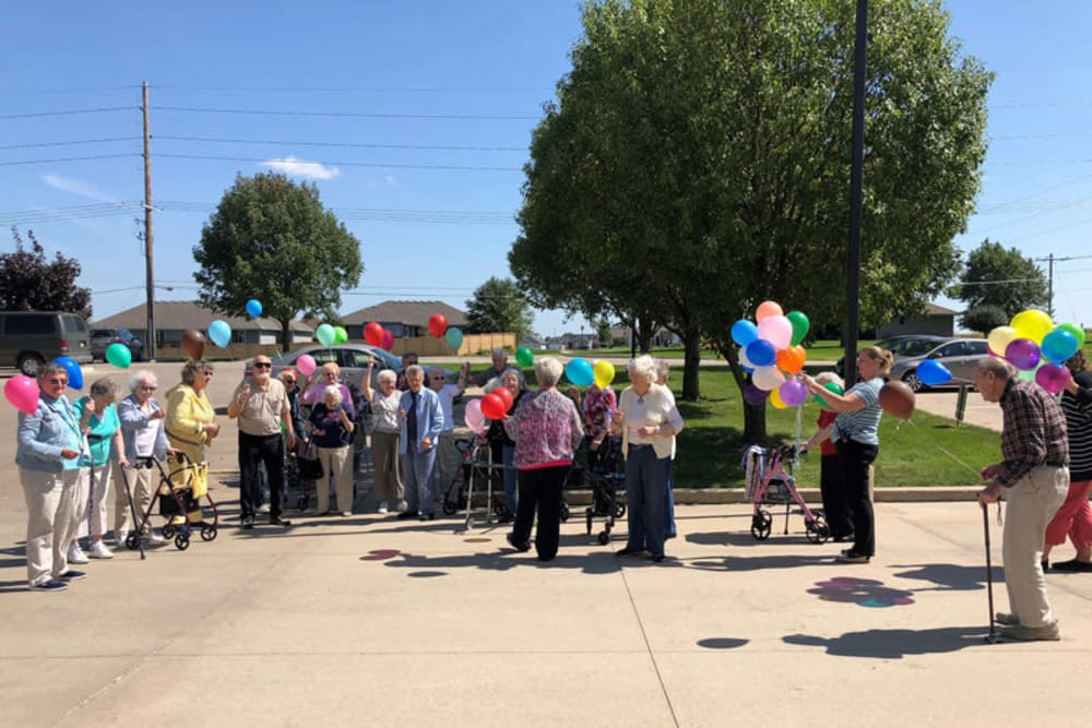 Residents celebrating with balloons at Glenwood Place in Marshalltown, Iowa.