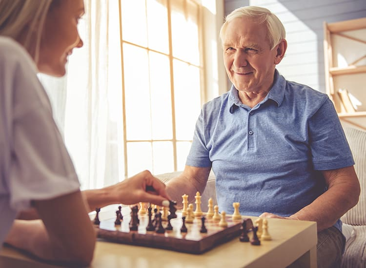 Happy resident engaging in a challenging chess match at Canoe Brook Assisted Living