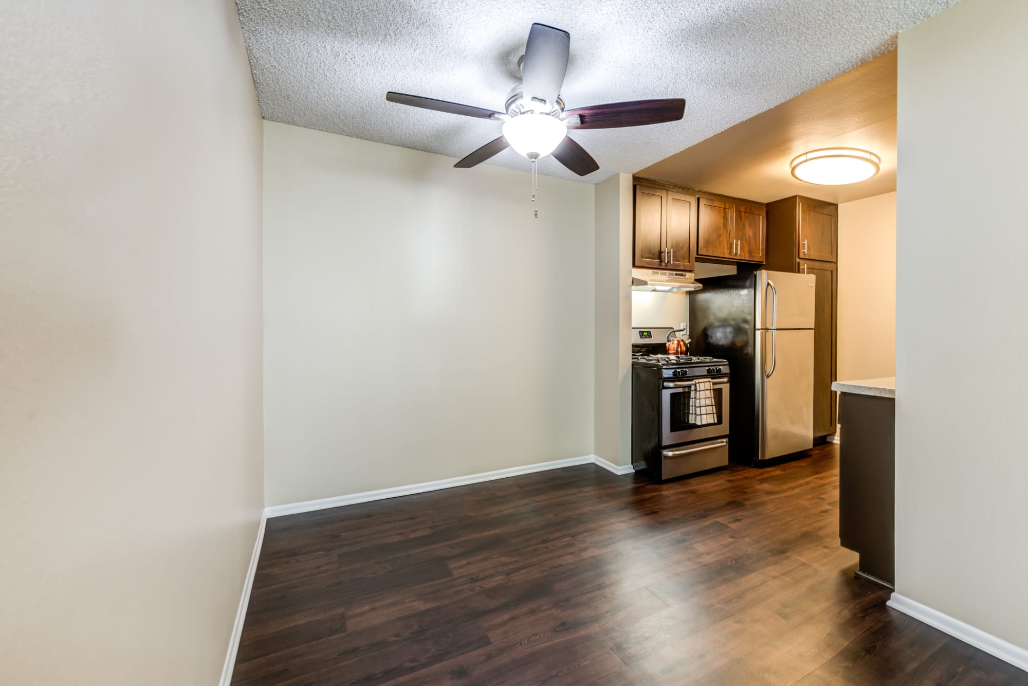 Living Room And Kitchen With Hardwood Floors At Kendallwood Apartments