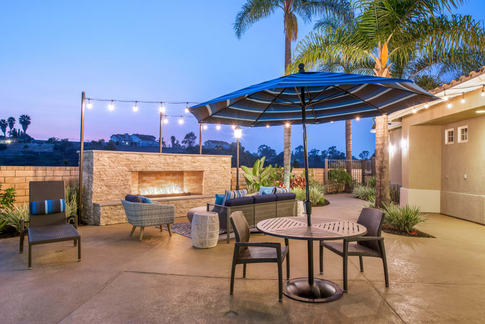 Table with umbrella by outdoor fireplace at Sofi Highlands in San Diego, California