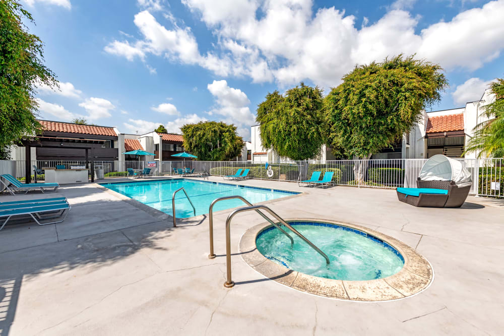Beautiful resort-style swimming pool with lounge chairs and a barbecue area at Kendallwood Apartments in Whittier, California