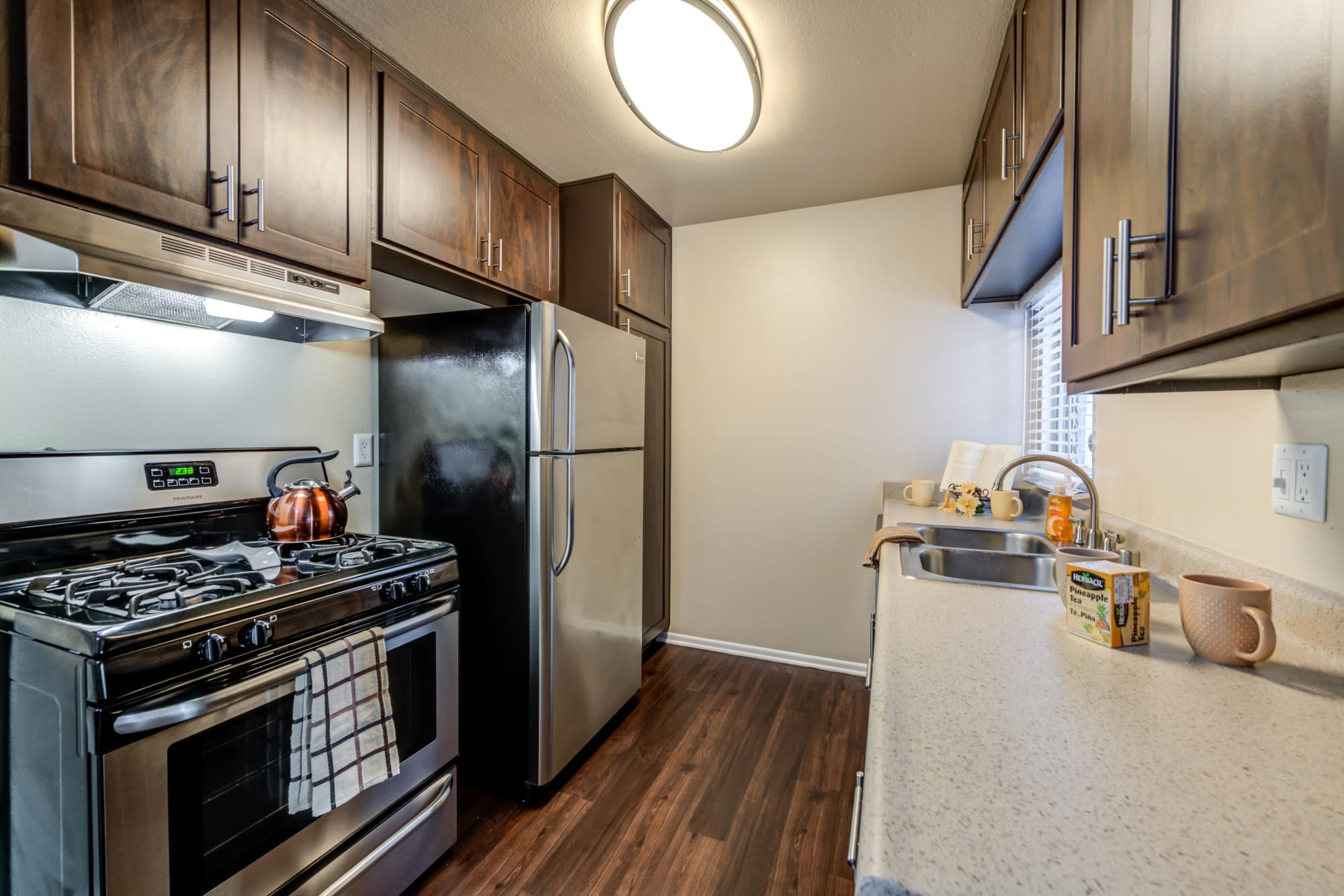 Renovated kitchen with brown cabinets and stainless steel appliances at Kendallwood Apartments in Whittier, California