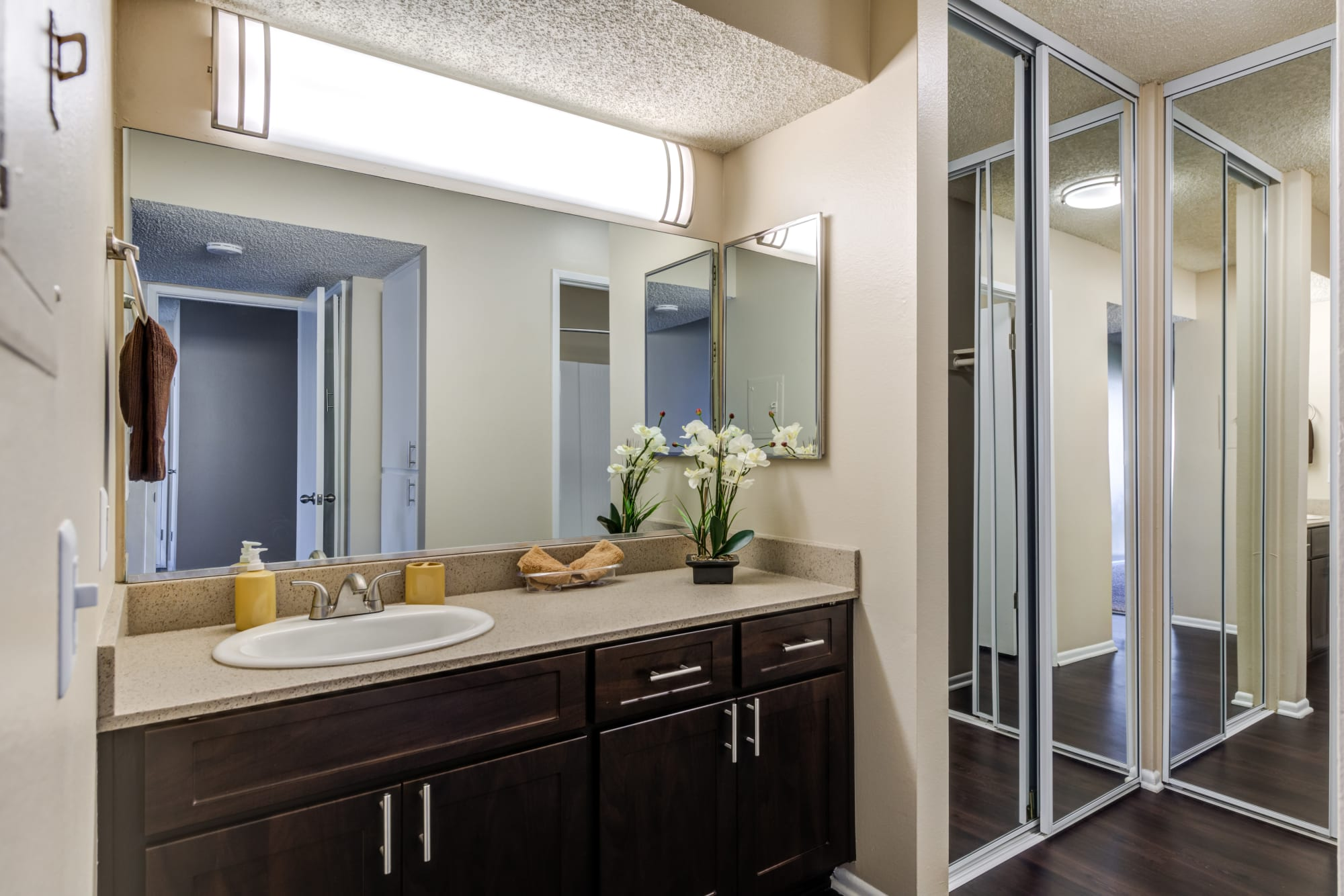 A renovated bathroom with brown cabinets, a large vanity and a mirrored closet door at Kendallwood Apartments in Whittier, California