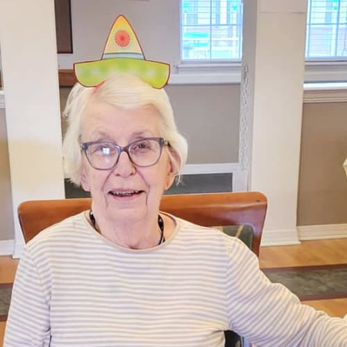 A resident sitting at a table with a fun hat on at Homestead House in Beatrice, Nebraska
