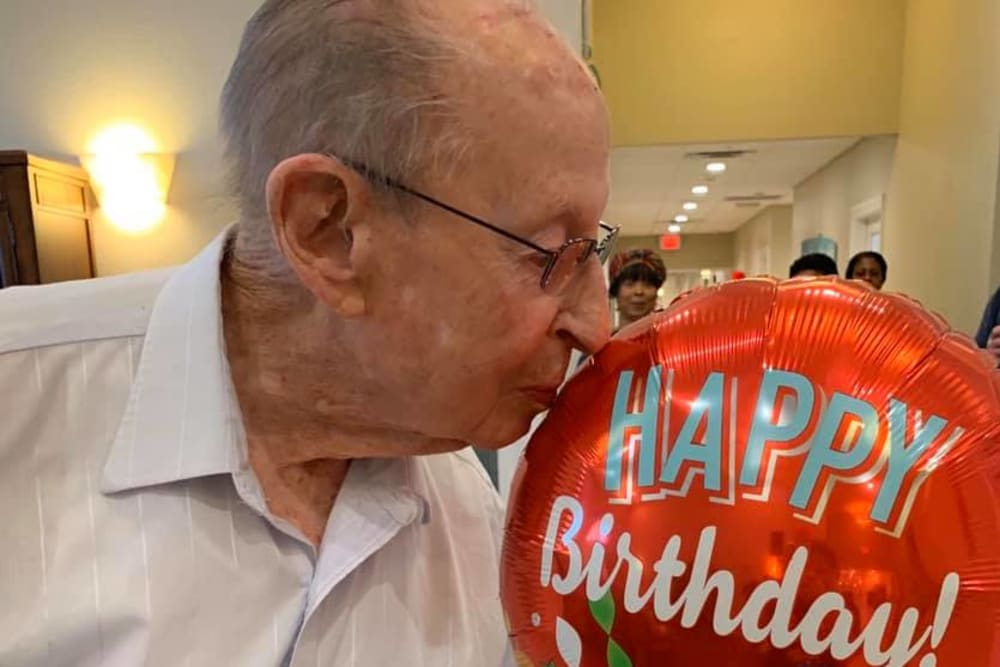 A resident kissing a Happy Birthday balloon at Inspired Living in Bonita Springs, Florida.