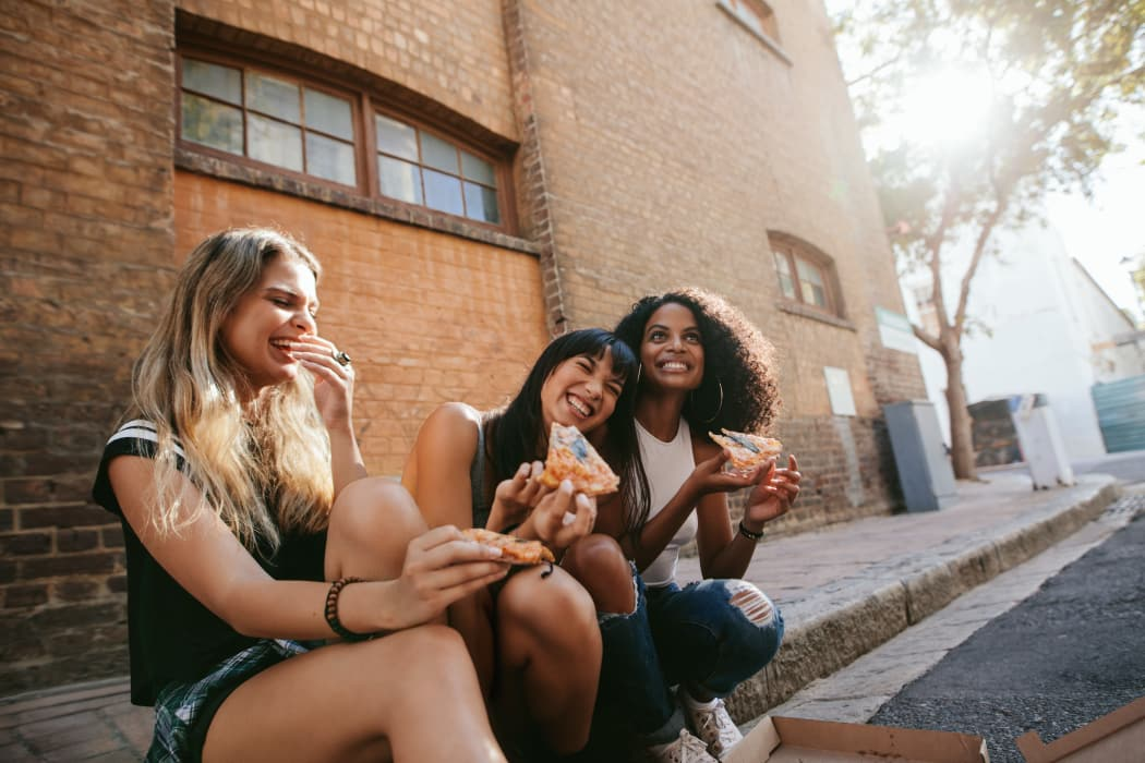 Friends eating pizza on the street near Ridgeview Place in Irving, Texas