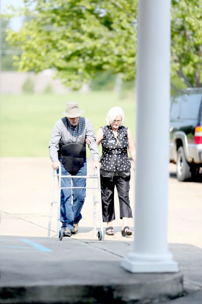 A staff member walking with a resident outside at Providence Assisted Living in Batesville, Mississippi