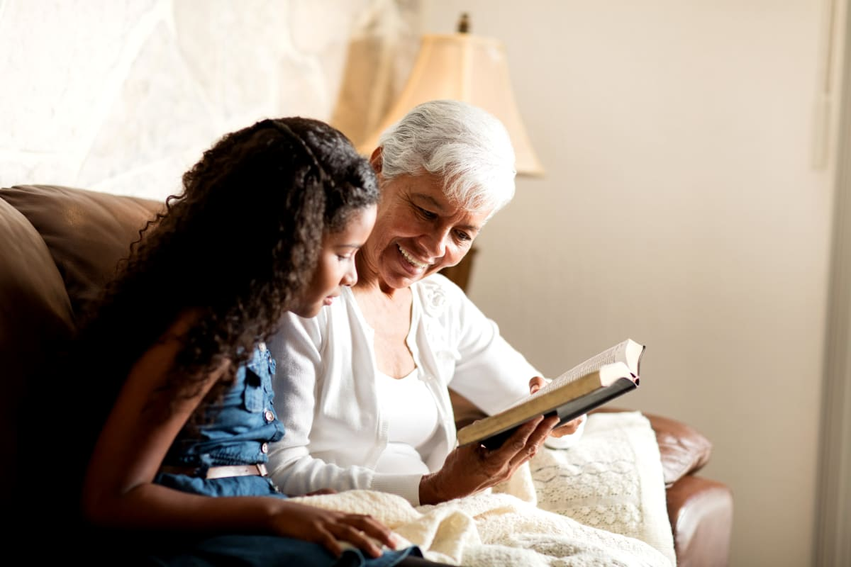 A resident and child reading a book together at Brightwater Senior Living of Tuxedo in Winnipeg, Manitoba