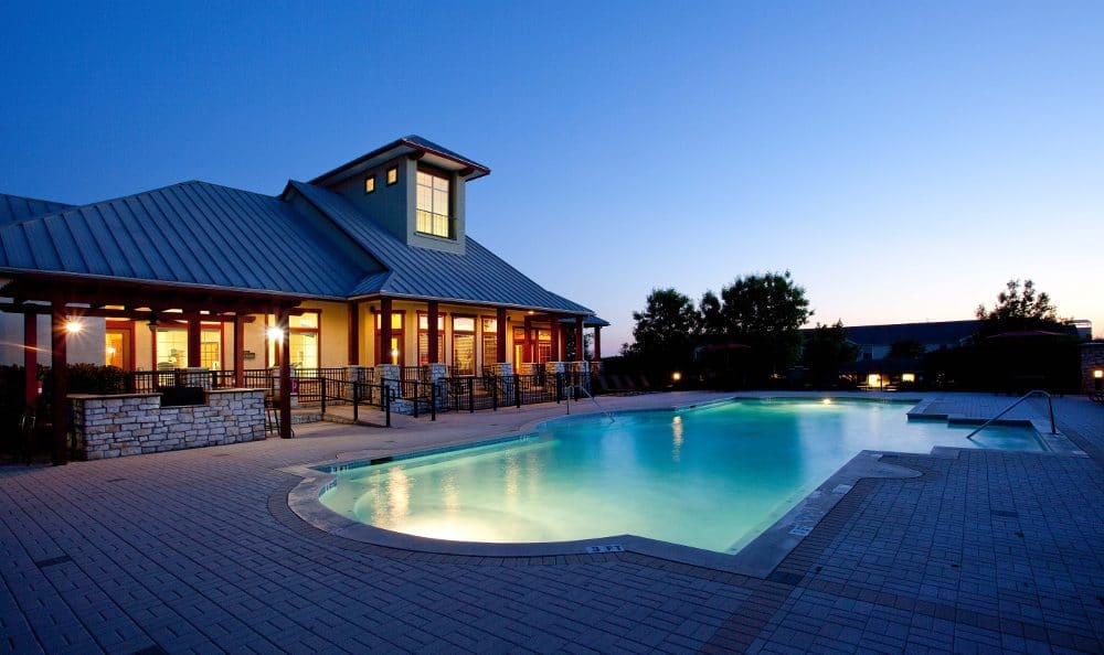 Clubhouse  pool at night at Springs at Live Oak Apartments