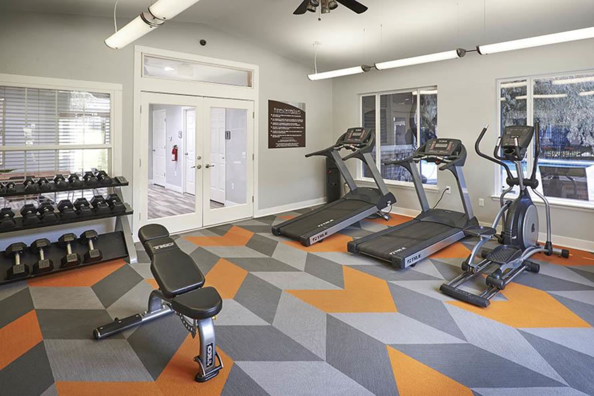 Fitness center with free weights and cardio machines at Crossroads at City Center Apartments in Aurora, Colorado
