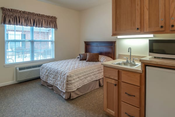 Assisted living apartment bedroom at La Bonne Maison Senior Living in Sikeston, Missouri