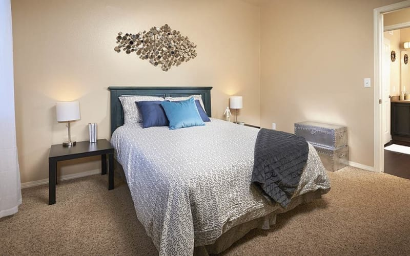 Spacious master bedroom with plush carpeting at Crossroads at City Center Apartments in Aurora, Colorado