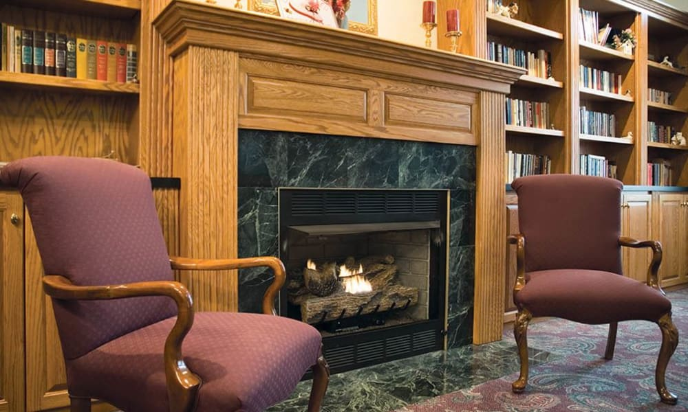 Two chairs next to a fireplace in a common area at Randall Residence of Decatur in Decatur, Illinois