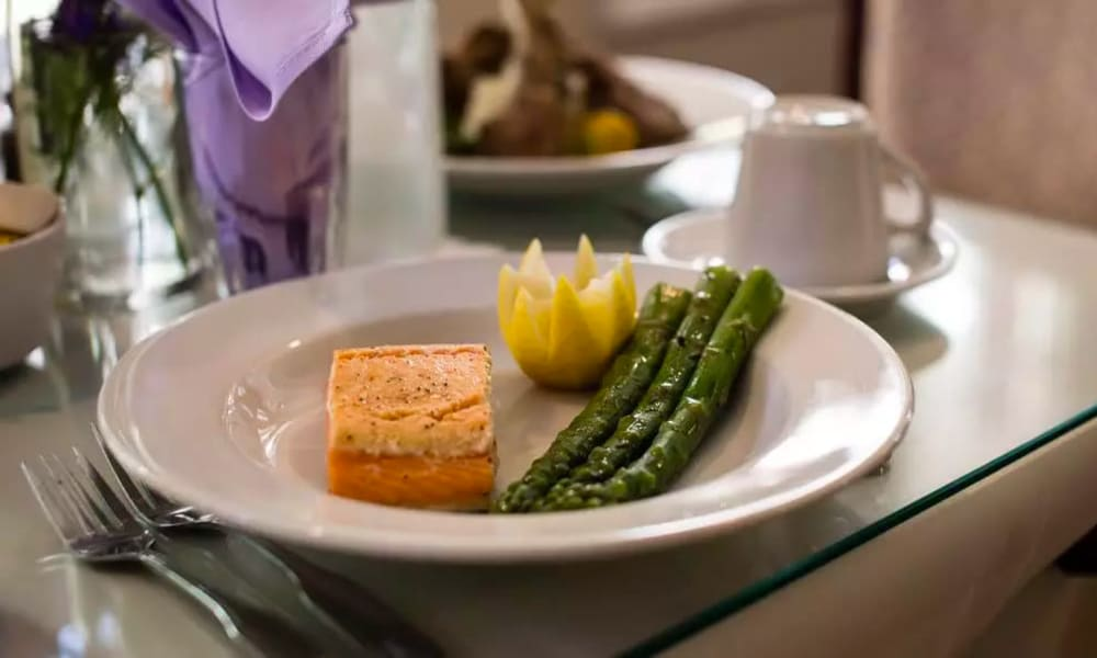 Delectable salmon and asparagus dish served in our restaurant-style dining hall at Carmel Village in Fountain Valley, California
