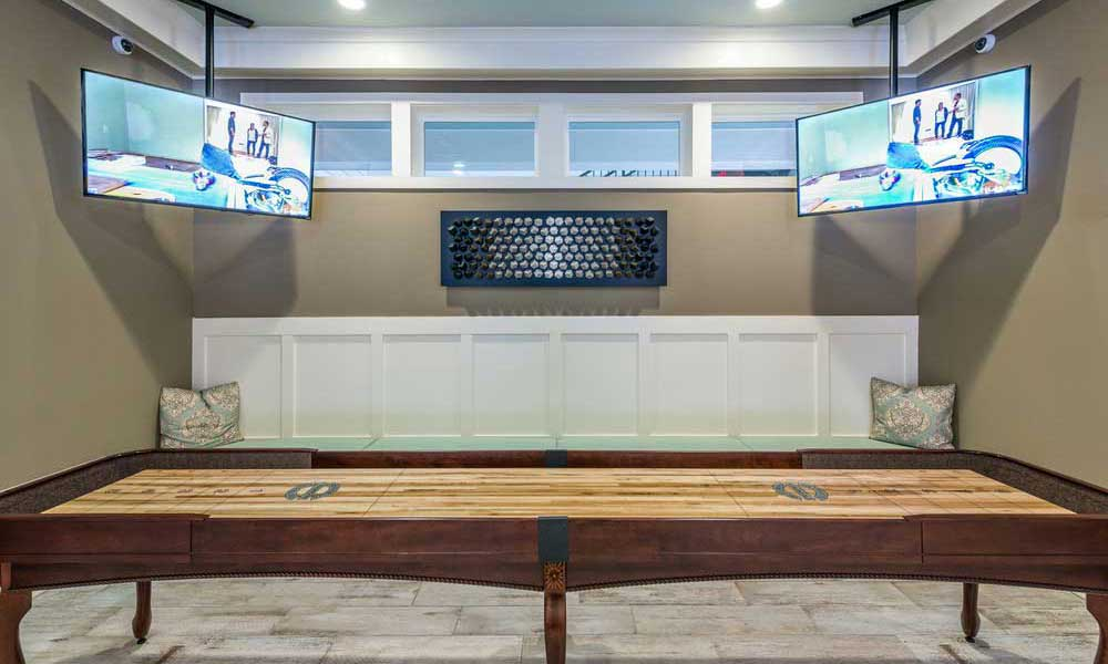 Tabletop shuffleboard and flatscreen TVs in the clubhouse game room at Alaqua in Jacksonville, Florida